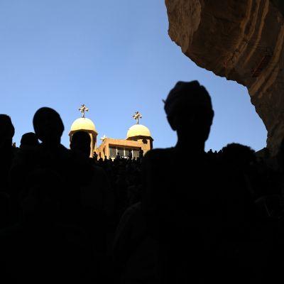Tummia hahmoja luvan etualalla, taustalla näkyy koptikristittyjen luostarin torneja.