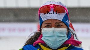 Krista Pärmäkoski står i målområdet iklädd munskydd och gulblå jacka med skidglasögon på huvudet.