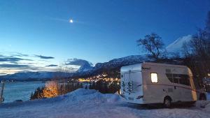 En husbil nere vid ett berg i ett vintrigt landskap.