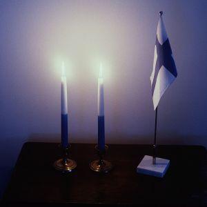 Finlands flagga och brinnande ljus.