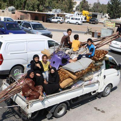 Siviilit pakenevat Idlibin maakunnassa Syyriassa, auton lavalla seitsemän ihmistä, patjoja ja huonekaluja.