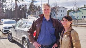 En man och en kvinna står på en parkeringsplats.