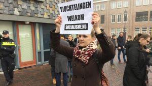 Ung holländsk kvinna håller upp plakat där hon önskar flyktingar välkomna i staden Spijkenisse där den högerpopulistiska kandidaten Geert Wilders inledde sin valkampanj den 18 februari 2017.