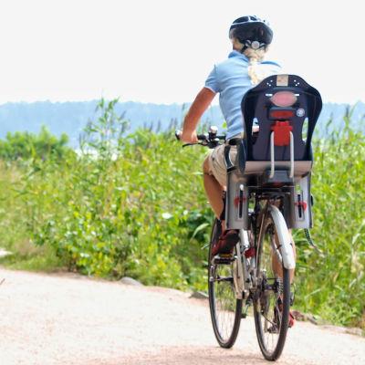 En kvinna cyklar med en cykel som har en cykelstol bakpå. Det är sommar.