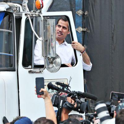 Juan Guaido tervehtii ihmisiä Kolumbian Cucutassa. Hänen vasen kätensä on tarttunut valkoisen rekan ohjaamon oven karmiin.