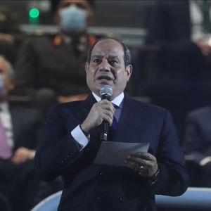 En man talar i mikrofon, i bakgrunden två män till.