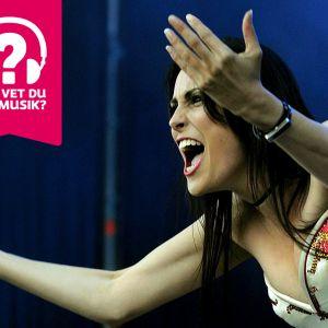 Sångerskan Sharon den Adel från bandet Within Temptation grimaserar och sträcker ut armarna framför sig.