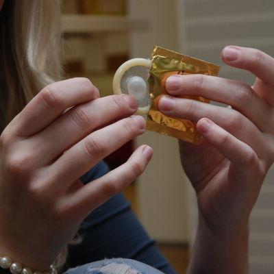 Tar ut kondom ur förpackning