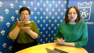 Teckenspråkstolken står till vänster, stadsdirektören till höger, bakgrunden är blå med liljan från Åbos stadsvapen.