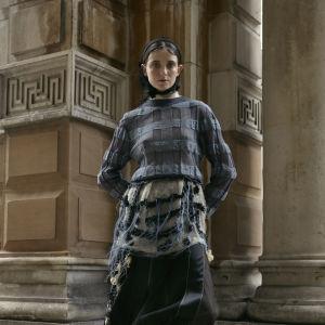 En modell poserar iklädd mörka kläder och en huvudduk framför en gammal och pampig husfasad.