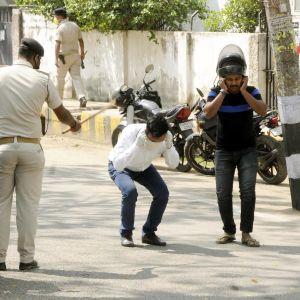 Poliisi heiluttaa keppiä ihmisten edessä