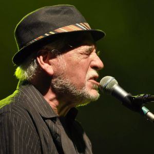 Gary Brooker har hatt på huvudet, slutna ögon och sjunger i en mikrofon.