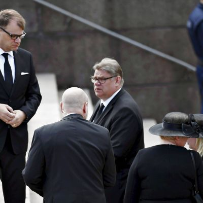 Turvamies seuraa vierestä, kun pääministeri Juha Sipilä ja ulkoministeri Timo Soini saapuvat siunaustilaisuuteen Tuomiokirkkoon presidentti Mauno Koiviston valtiollisissa hautajaisissa Helsingissä 25. toukokuuta 2017.