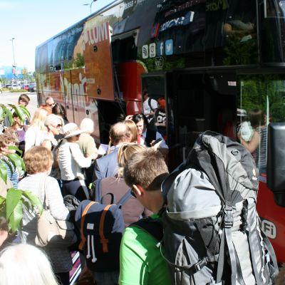 Matkustajia menossa linja-autoon.