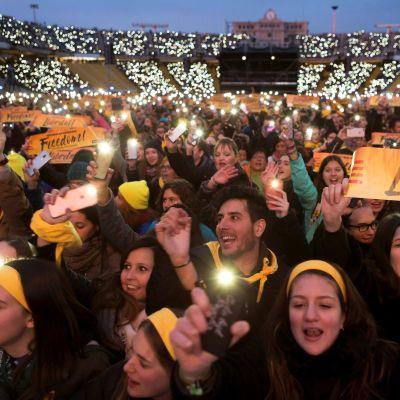 Ihmisiä Barcelonan olympiastadionilla, he vilkuttavat valoja älypuhelimellaan hämärtyvässä illassa.