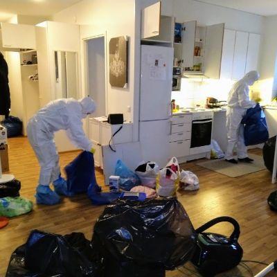 Kaksi henkilöä lajittelee suojapuvuissa ja hengityssuojaimissa homeasunnossa tavaroita.