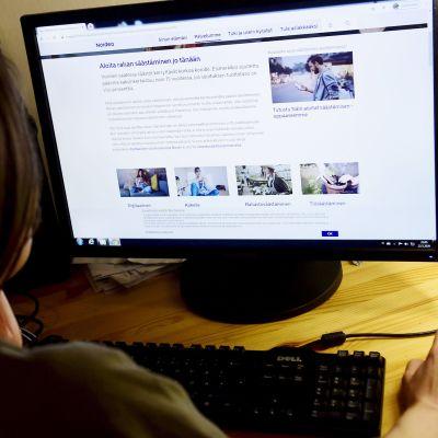 Nainen tutkii  Nordean verkkosivuja.