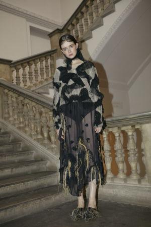 En brunhårig modell iklädd mörka kläder står i en gammal trappa och poserar.