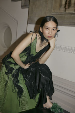En modell sitter i en trappa iklädd en svartgrön klänning och huvudduk.