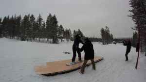 Kvinna gör snowboardtricks och glider på en ramp