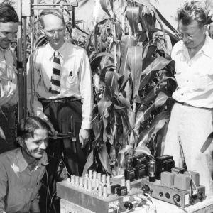 Verner Suomi maissipellolla työryhmineen tekemässä mittauksia