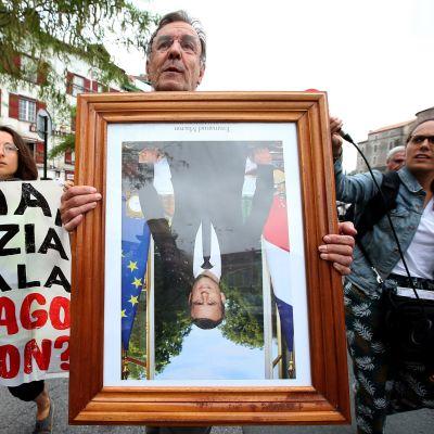 Mielenosoittaja pitelee Macronin muotokuvaa ylösalaisin.
