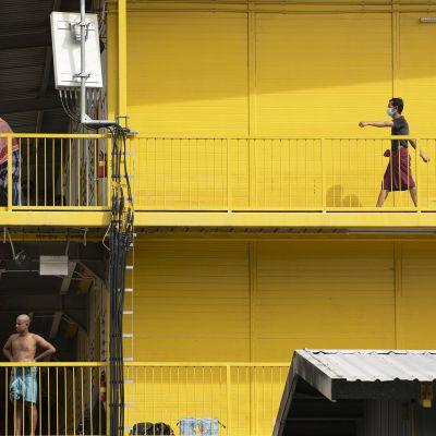 Siirtotyöläisiä asuintalonsa luhtikäytävällä Singaporessa.