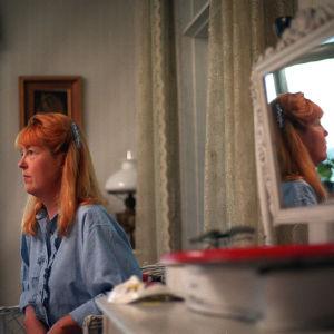 Näyttelijä Leena Uotila istuu huvilan kamarissa sivuttain: kuva heijastuu myös hänen takanaan seinällä olevasta peilistä.
