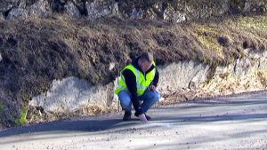 Man på huk inspekterar grusväg.