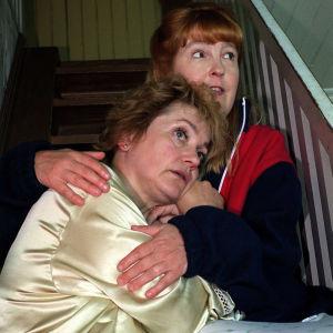 Rea Mauranen (Maria) nojaa Leena Uotilan (Fridan) rintaan peloissaan puutalon portaikossa.