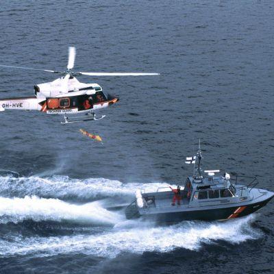 En sjöbevakningshelikopter och en sjöbevakninsbåt åker vid sidan om varandra.