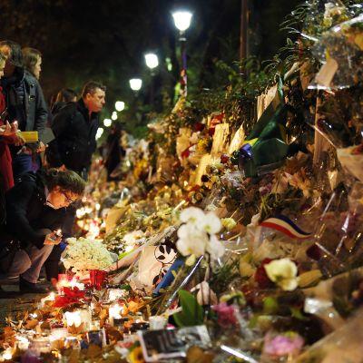 Ihmiset toivat kukkia ja kynttilöitä muistopaikalle lähelle Bataclan -konserttisalia, Pariisissa 20. marraskuuta.