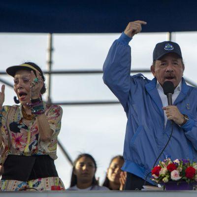Presidenttipari puhuu korokkeella . Vaimo taputtaa käsiään, presidentti heristää sormeaan.