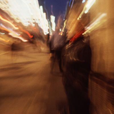 Ung person står ensam på gatan, omgivnngen är suddig, personen verkar finnas i ett rus.