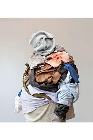 valokuva naisesta jonka päällä iso kasa vaatteita
