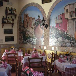 Tyypillinen eteläitalialainen ravintolasali Sisiliassa: pöydillä punavalkoiset pöytäliinat ja servetit, seinamaalauksissa kylämaisemia.