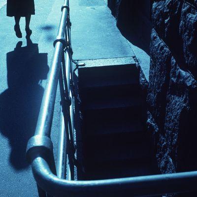 En ensam kvinna går på en mörk gata