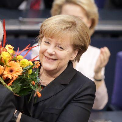 Angela Merkel vastaaottaa kukat parlamentissa tultuaan valituksi kolmannelle kaudelleen liittokanslerina.