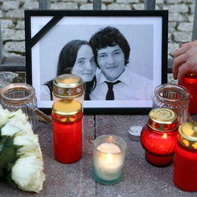 Ján Kuciakin ja Martina Kušnírován mustakehyksinen valokuva, jonka ympärille on tuotu kynttilöitä.