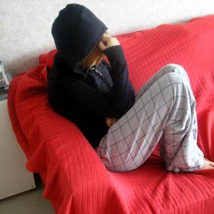 Ung person som döljer sitt ansikte i en huva sitter på soffan