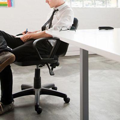 Mies istuu työtuolissa ja kirjoittaa muistiinpanoa