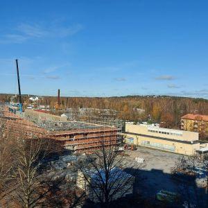 Rakenteilla oleva Kaurialan koulu syksyisenä päivänä. Punatiilisen uudisrakennuksen ympärillä on rakennustelineitä. Taustalla kaksi keltaista rakennusta. Kuva otettu viereisen talon seitsemännestä kerroksesta 19.lokakuuta 2021.