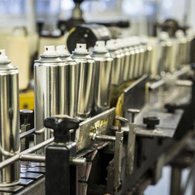 Aerosolipulloja liukuhihnalla tehtaalla.