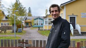 En man i svart jacka står utanför porten till ett daghem, en träbyggnad i gult och blått. Mannen tittar in i kameran och ler.