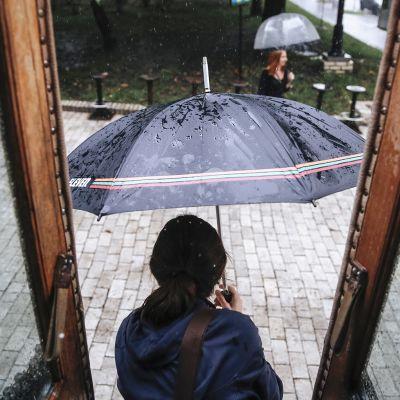 Nainen astuu ulos sateeseen Kiovassa, Ukrainassa.