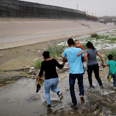 Siirtolaiset juoksevat rajan yli.