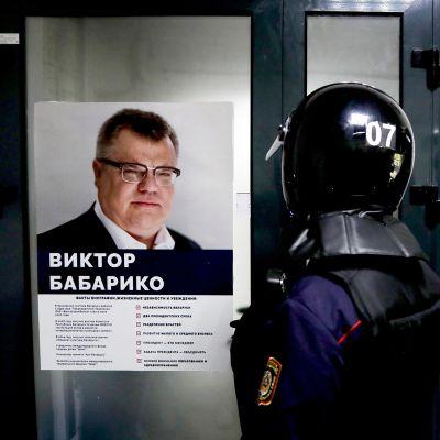 Mellakkavarusteisiin pukeutuneet poliisit seisovat Viktor Babarykon kampanjajulisteen edustalla mINSKISSÄ.