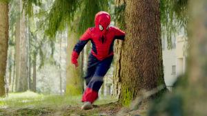 Lapsi Spiderman-puvussa juoksee metsässä.