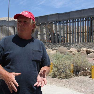 Punaiseen Make America Great Again -lippalakkiin sonnustautunut mies seisoo raja-aidan edessä.