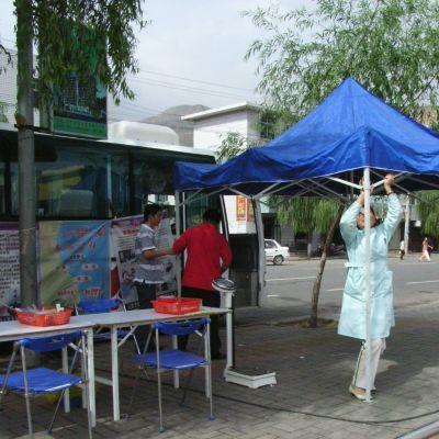 En buss med ett tält utanför som två sjukvårdare reser.